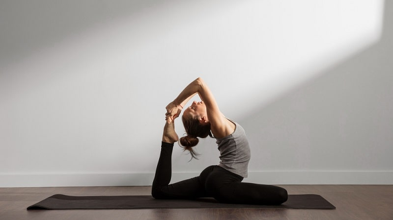 A woman maintaining her form while holding her yoga pose on a dark gray yoga mat indoors.