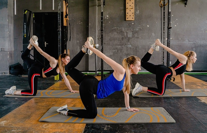 A group of women showing proper form and flexibility while holding their yoga pose on their printed yoga mats indoors.