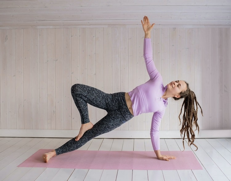 A woman demonstrating endurance and flexibility while holding her form during a yoga pose on her pink yoga mat indoors.