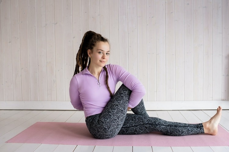 A woman showing endurance while maintaining her form during Seated Twist Pose on a pink yoga mat indoors.