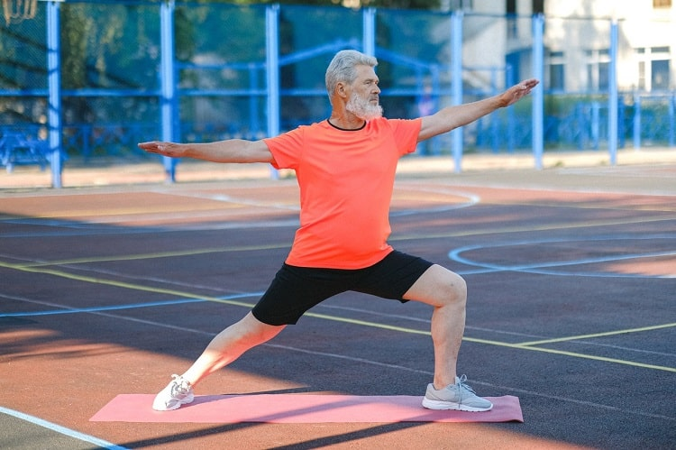 A senior man standing on a pink yoga mat, holding Warrior Pose 2 on an outdoor court.