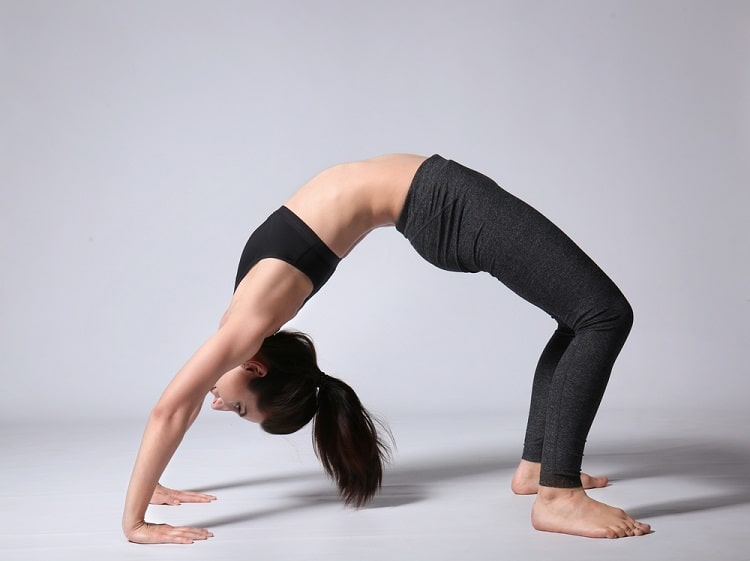 A woman showing perfect form and endurance while holding Wheel Pose on a bare white floor.