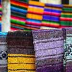Mexican blankets with a gray-dominant color palette in focus, along with multi-colored ones in the background.