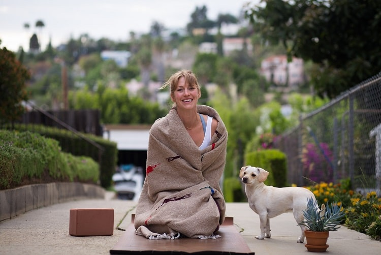 A woman wrapped in a Mexican blanket with a taupe base and red and black prints, while sitting on a brown yoga mat and her dog beside her.