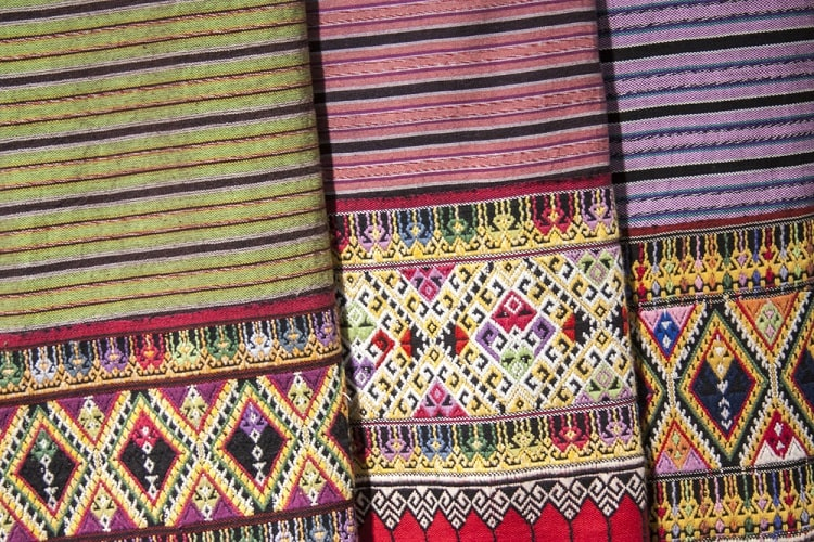 Striped green, red, and purple Mexican blankets with intricate multi-colored woven designs on the edges.