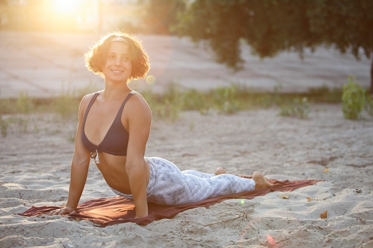 A smiling woman doing Cobra Pose on a brick red Mexican blanket placed on the sand.