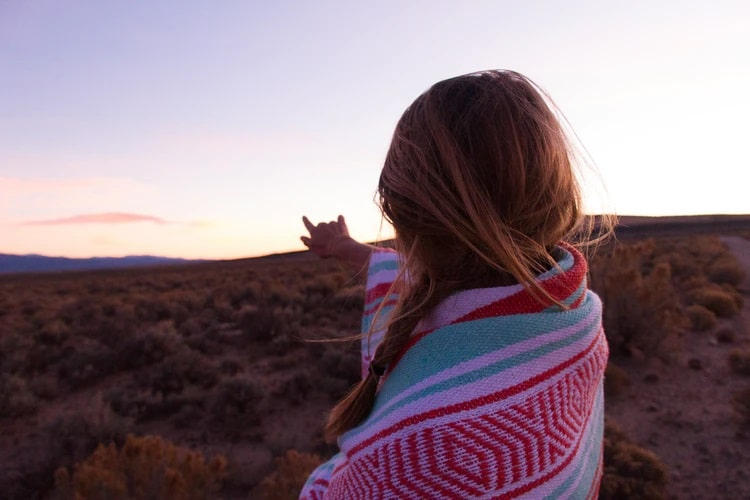 A woman with a Mexican blanket wrapped around her, with one hand extended toward a view of the mountainside.