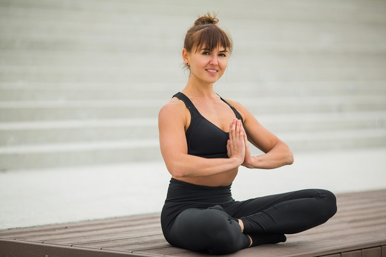 A smiling woman with praying hands during a sitting yoga pose.