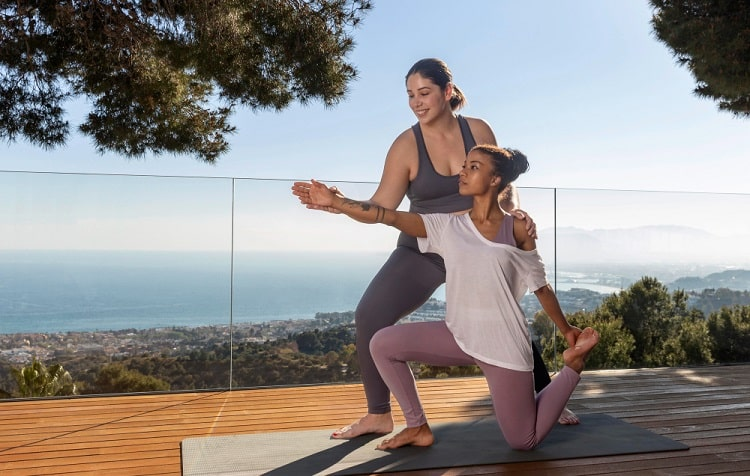 A female yoga instructor helping her student achieve the proper yoga pose on a gray yoga mat outdoors.