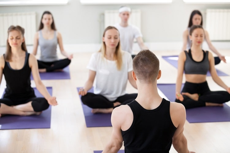 A male yoga instructor leading his class during a breathing and meditation session.