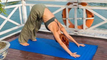 A woman doing a yoga pose on a bright blue yoga mat on a cruise deck.