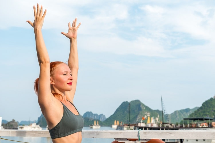 A woman in a gray top doing a sun salutation right by a cruise deck.