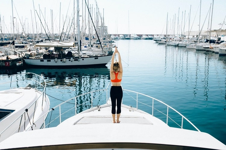 A woman in an orange top and black leggings with arms outstretched toward the sky, standing by a cruise deck.