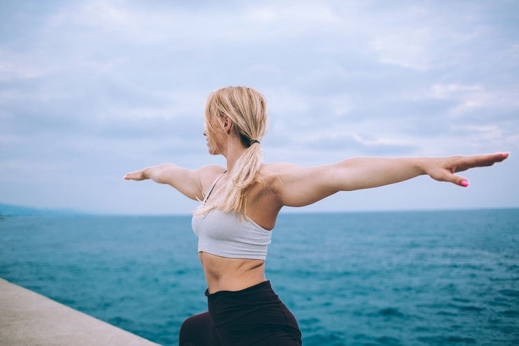 A woman in a white top and black leggings doing a yoga pose right by the calm blue sea.