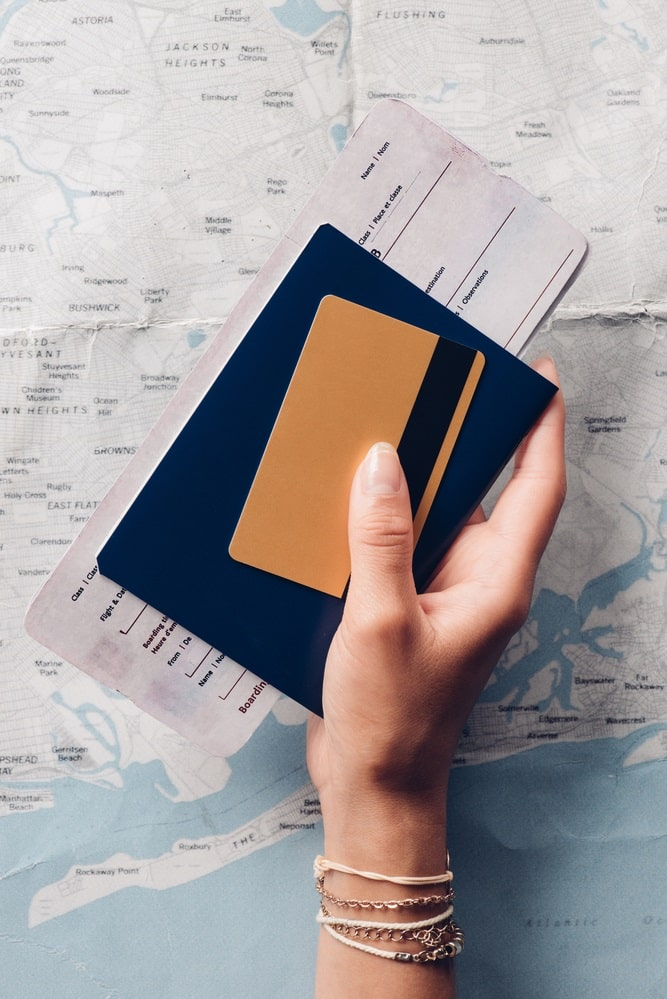 A female hand holding a passport, travel ticket, and credit card, with a creased map in the background.