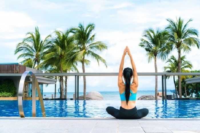 A woman doing a sitting yoga pose at the edge of a pool with her arms raised doing a sun salutation, while facing the clear blue sky.