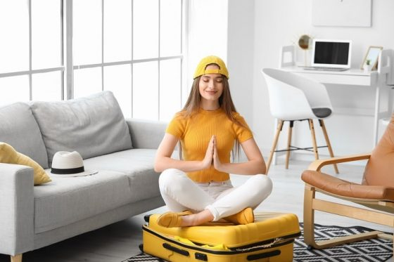 A woman in a yellow shirt and matching cap, sitting on her suitcase in a meditative yoga pose.
