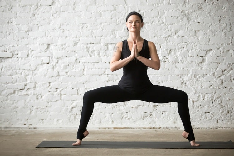 A woman doing Goddess Pose for Forrest yoga on a dark gray yoga mat against a textured white wall.
