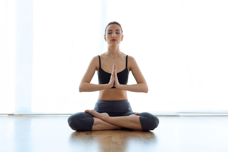 A woman in Lotus Pose reconnecting with herself during a Forrest yoga session indoors.