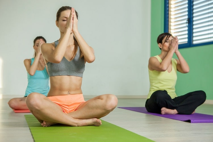 A group of women meditating with praying hands during an indoor yoga session.