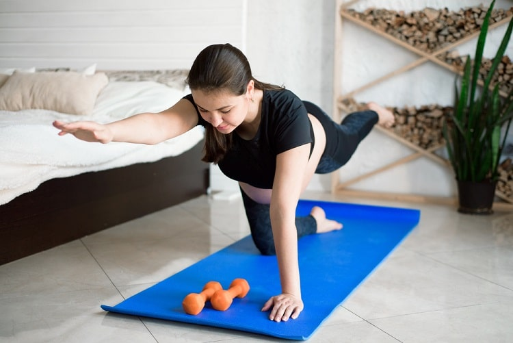 A woman doing Standing Forward Bend on a blue yoga mat with her orange dumbbells in front of her.