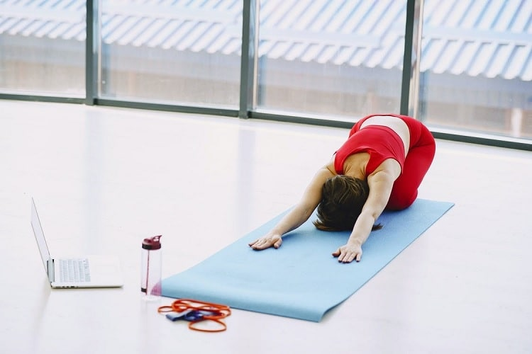 A woman doing Child's Pose on a light blue yoga mat with her resistance band and water bottle on the side.