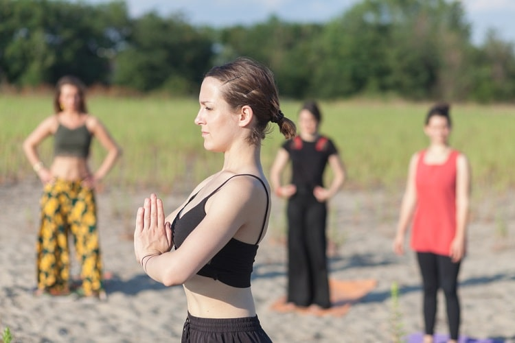 A female yoga instructor practicing yoga outdoors with her students.