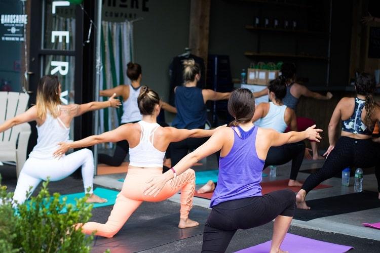 Yoga students doing Warrior 2 Pose on their yoga mats at a yoga studio.