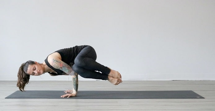 A woman with a sleeve tattoo, doing an advanced yoga handstand.