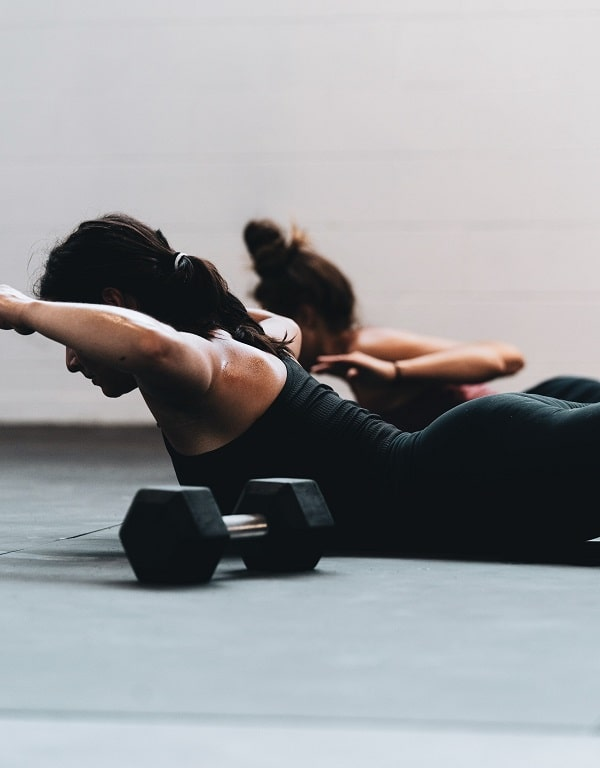 A woman doing a core strengthening exercise on the floor with a dumbbell to her side.