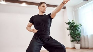 A man practicing karate inside a martial arts hall with wooden floors and a potted plant in the corner.