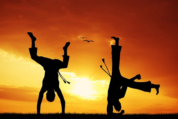 A silhouette of two males in capoeira stance against a sunset backdrop.