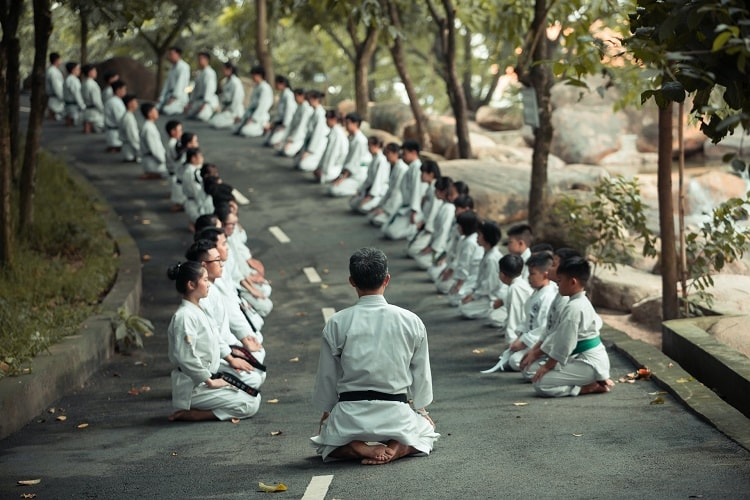 A martial arts class of young students with their instructor leading the group and everyone seated on the road facing each other.