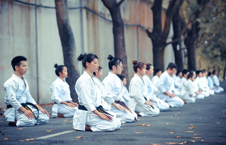 A martial arts class of young students seated on the ground with dried leaves, with hands on their laps, meditating.