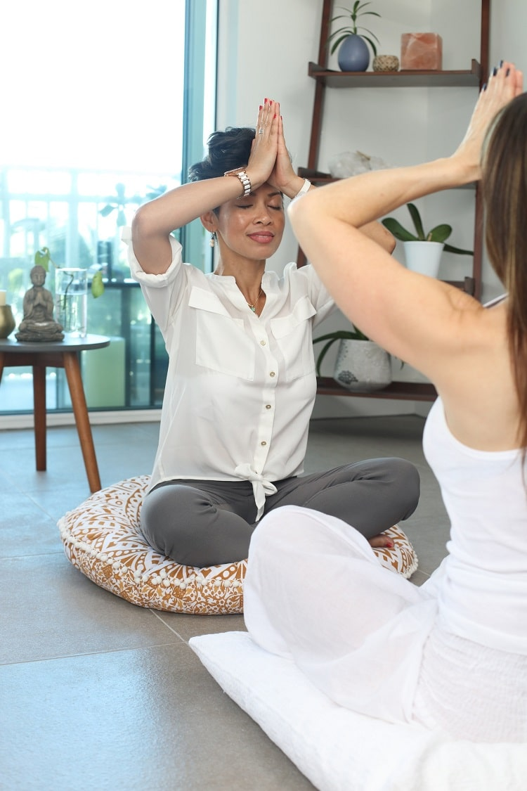 A woman with praying hands pressed to her forehead while facing her instructor during a yoga session.