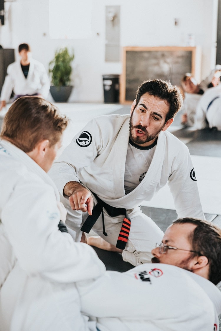 A martial arts instructor coaching his two students during combat practice in class.