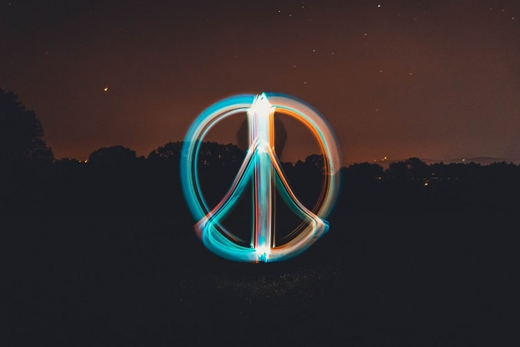 A peace symbol illuminated in the dark against a starry sky.