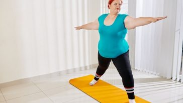 A plus-size woman doing Warrior 2 pose on a bright yellow yoga mat indoors.