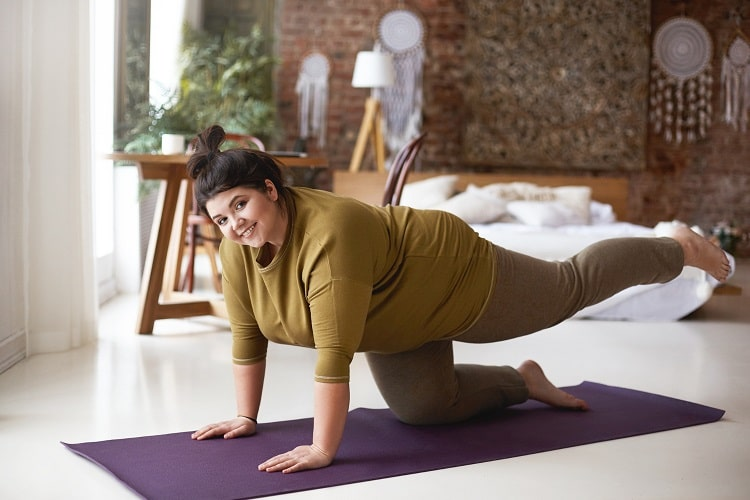 A plus-size woman in the middle of doing Table Pose on a purple yoga mat indoors.