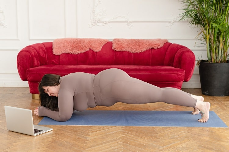 A plus-size woman doing Dolphin Plank Pose on a dusty-blue yoga mat in a living room with a velvet red couch.