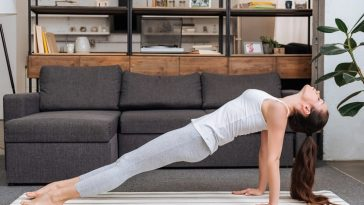 A woman doing Bridge Pose on a striped yoga mat inside the living room beside a dark gray couch.
