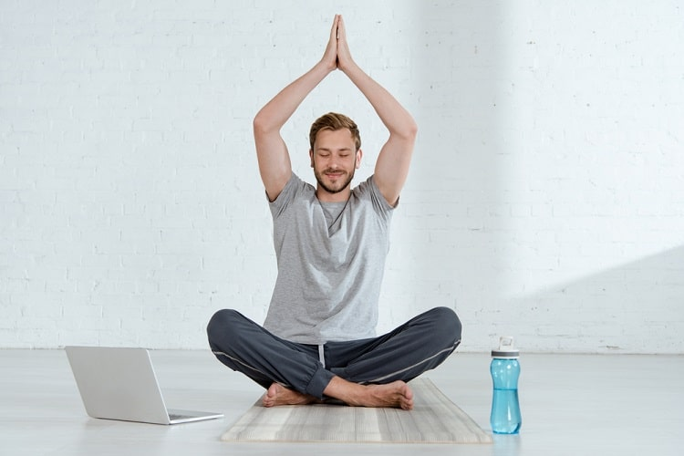 A man doing Half Lotus Pose with his eyes closed, with his laptop to his right and water bottle to his left.
