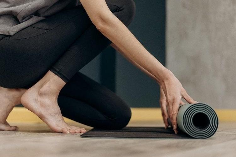 A woman in black leggings unrolling a dark gray yoga mat on a wooden floor.
