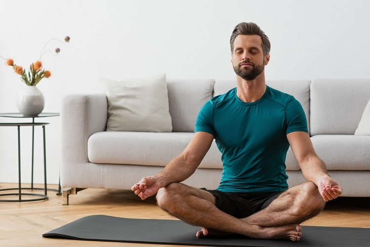 A man looking relaxed while meditating with closed eyes in a sitting yoga pose on a dark gray yoga mat inside a living room.