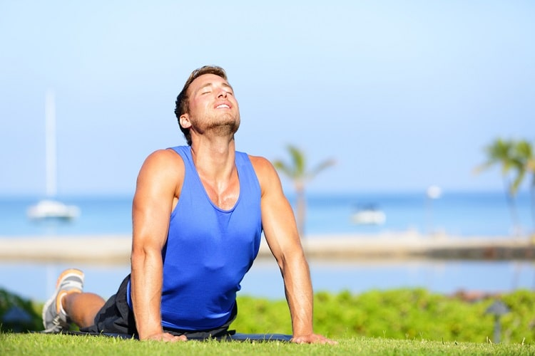 A man in a blue shirt looking relaxed, while doing Cobra pose on a grassy lawn, with a seascape view in the background.