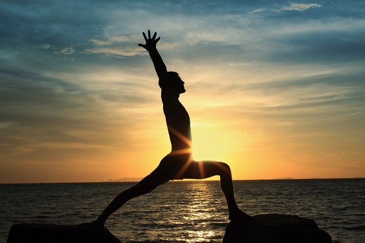 A fit man doing a standing yoga pose on two separate rocks, with arms raised to the sky and the sunset in the background.