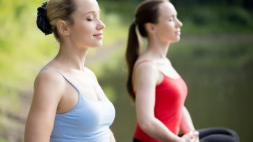 Two women looking calm and relaxed while doing a yoga breathing meditation in an open field.