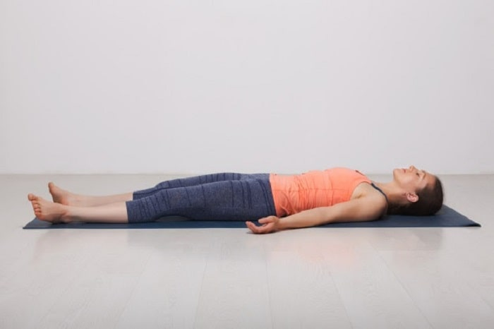 A woman doing Savasana or Corpse Pose on a dark gray yoga mat in an indoor studio.