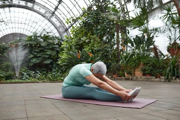 A woman doing Paschimottanasana or Seated Forward Fold on a purple yoga mat inside a botanical garden.