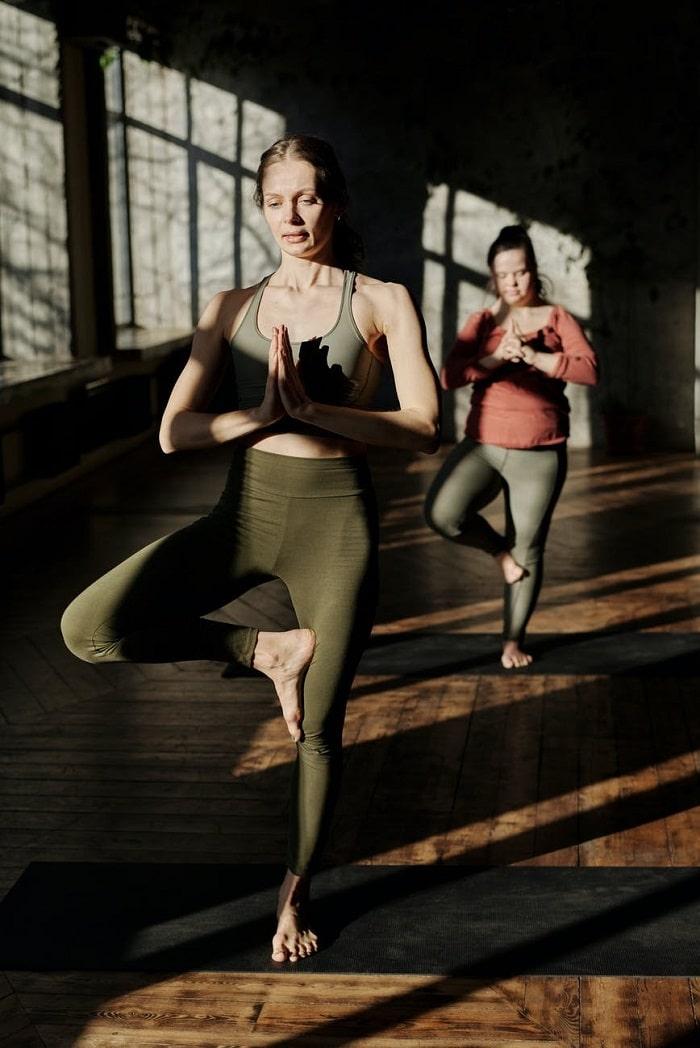 Two women doing Vrikshasana or Tree Pose on their dark gray yoga mats inside a fitness studio.